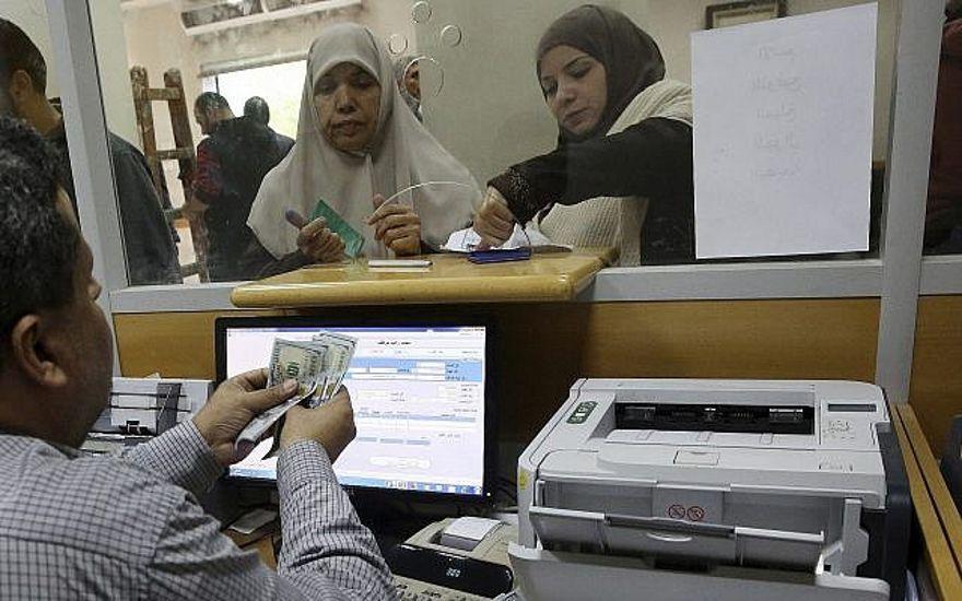 Un empleado del gobierno designado por Hamas en Gaza firma un documento para recibir el 50 por ciento de su salario atrasado de los fondos donados por Qatar, mientras que otros esperan en la cola, en la oficina principal de correos de Gaza, en la ciudad de Gaza, el 7 de diciembre de 2018. (Foto AP / Adel Hana)