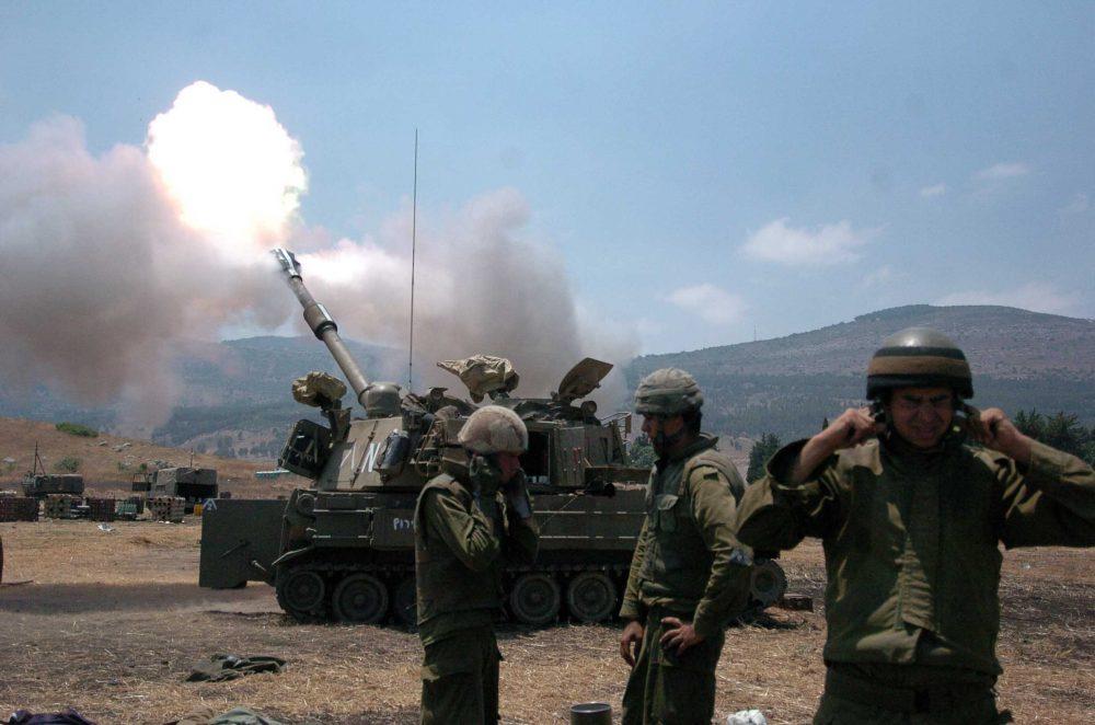 Los soldados israelíes se tapan los oídos mientras un obús dispara en el Líbano desde Kiryat Shemona el 20 de julio de 2006 durante la Segunda Guerra del Líbano. Crédito: Guy Assayag / Flash90.