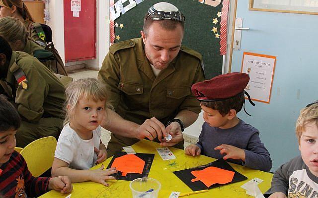 Un soldado en el programa de conversión de Nativ que visita un jardín de infantes en el asentamiento de Efrat para aprender sobre la festividad judía de Hanukkah el 7 de noviembre de 2013. (Gershon Elinson / Flash90)