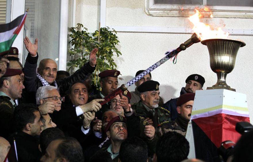 El presidente de la Autoridad Palestina, Mahmoud Abbas, enciende una antorcha conmemorativa en Ramallah el martes temprano. (Crédito de la foto: Hadas Parush / Flash90)