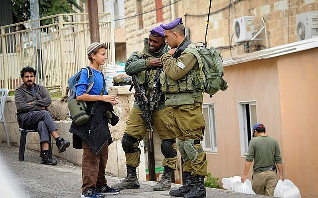 Soldados de las FDI hablan con un joven judío en la dividida ciudad de Hebrón, 6 de noviembre de 2015 (Mendy Hechtman / FLASH90)