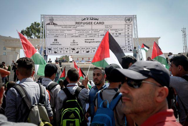 Los manifestantes palestinos agitan su bandera nacional frente a una tarjeta de refugiado gigante fabricada durante una protesta contra la decisión de Estados Unidos de recortar los fondos de la ONU a los palestinos en la ciudad de Belén, Cisjordania, el 26 de septiembre de 2018. Crédito: Wisam Hashlamoun / Flash90.