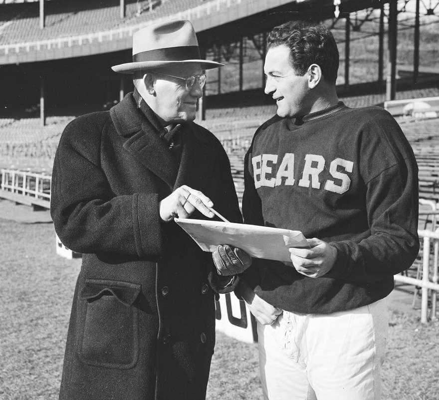 El entrenador de los Chicago Bears, George Halas, a la izquierda, y Sid Luckman, jugador de los Bears, son vistos en el Polo Grounds en Nueva York, el 14 de diciembre de 1946. (Foto AP)