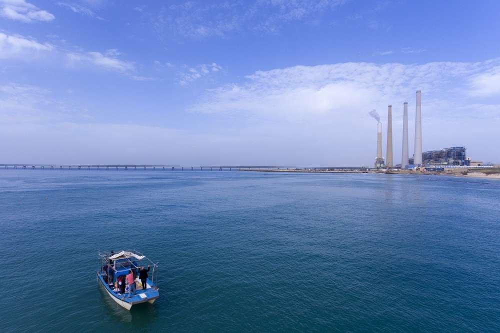 Los investigadores buscan tiburones en el mar Mediterráneo frente a la costa de Hadera, con la planta de energía Orot Rabin al fondo.(Foto AP / Ariel Schalit)