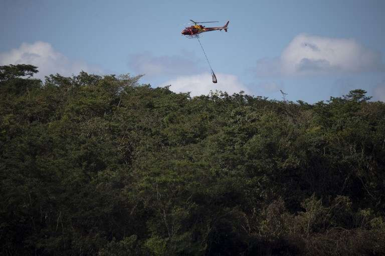 Un helicóptero de bomberos transporta el cuerpo de una víctima del colapso de la represa del viernes en una mina de mineral de hierro perteneciente a la gigante minera brasileña Vale, cerca de la ciudad de Brumadinho, Estado de Minas Gerais, sureste de Brasil, el 28 de enero de 2019. (Mauro PIMENTEL / AFP)