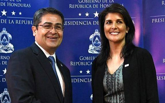 El reelegido presidente de Honduras, Juan Orlando Hernández (L) le da la mano a la embajadora de Estados Unidos ante las Naciones Unidas, Nikki Haley, antes de hablar con la prensa en Tegucigalpa, el 27 de febrero de 2018. (AFP PHOTO / Orlando SIERRA)