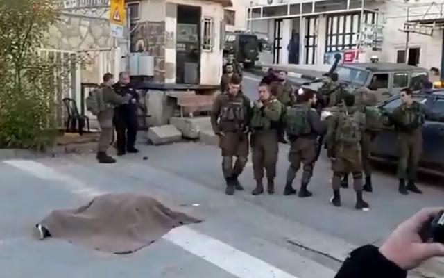 Soldados israelíes son vistos junto al cadáver de un presunto atacante disparado por tropas durante un intento de apuñalamiento cerca del asentamiento de Kiryat Arba en Cisjordania el 11 de enero de 2018. (Captura de pantalla: Twitter)