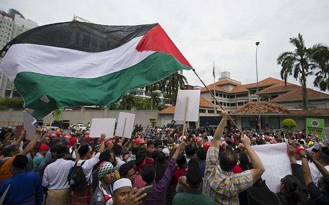 """Manifestantes ondean banderas """"palestinas"""" durante una protesta frente a la Embajada de los Estados Unidos en Kuala Lumpur, Malasia, el 8 de diciembre de 2017. (Foto AP / Vincent Thian)"""