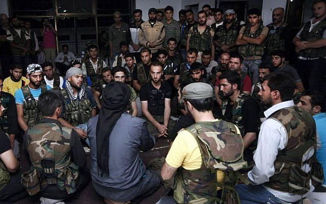 En esta foto del 29 de julio de 2012, los soldados del Ejército Sirio Libre se reúnen en la ciudad fronteriza de Azaz, a unos 32 kilómetros (32 millas) al norte de Aleppo, Siria. Hombres armados vinculados a Al Qaeda en el norte de Siria capturaron la ciudad cerca de la frontera con Turquía el jueves 19 de septiembre de 2013, luego de fuertes enfrentamientos con los rebeldes de la zona apoyados por Occidente, lo que llevó a Turquía a cerrar un cruce cercano, activistas y turcos. dijeron los funcionarios. (Foto AP / Turkpix, Archivo)