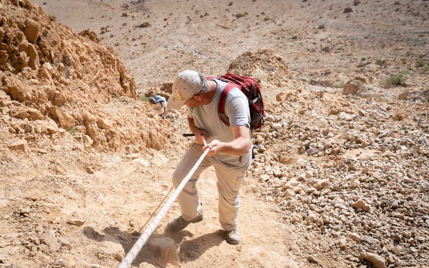 El investigador Oren Gutfeld desciende de la cueva 52, en el sitio arqueológico de Qumran, el 22 de enero de 2019. (Luke Tress / Times of Israel)