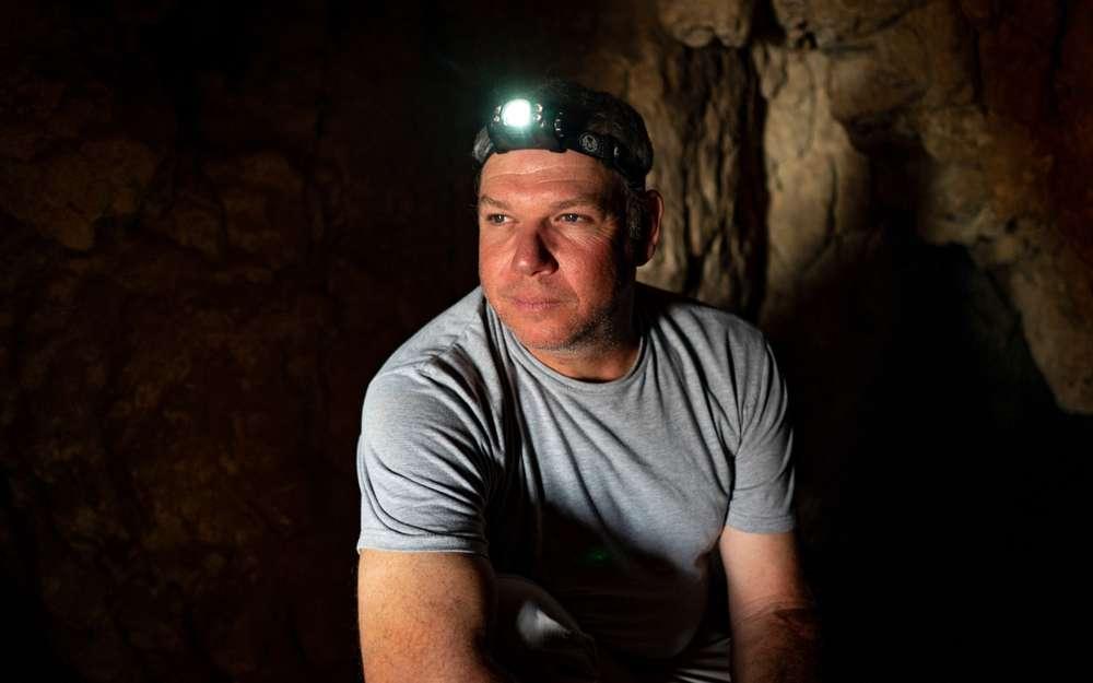 Investigador Oren Gutfeld dentro de la Cueva 52 en el sitio arqueológico de Qumran, 22 de enero de 2019. (Luke Tress / Times of Israel)