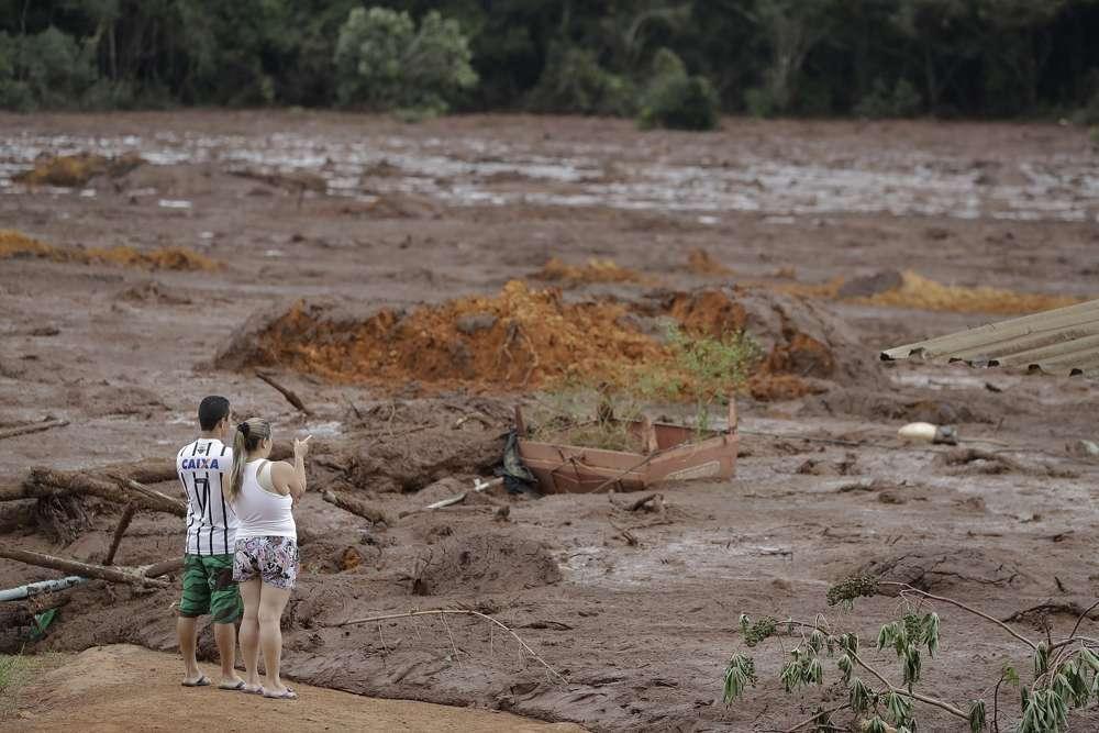 Una pareja con familiares desaparecidos mira el área inundada, después de que una presa se derrumbó en Brumadinho, Brasil, el sábado 26 de enero de 2019. (AP / Andre Penner)