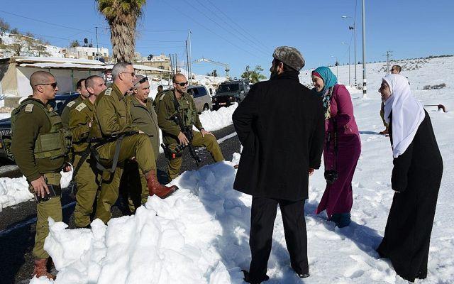 El entonces jefe de personal de las FDI, Benny Gantz, habla con una familia de palestinos a lo largo de la ruta 60 de la Ribera Occidental, el 15 de diciembre de 2013. (Judah Ari Gross / Fuerzas de Defensa de Israel)
