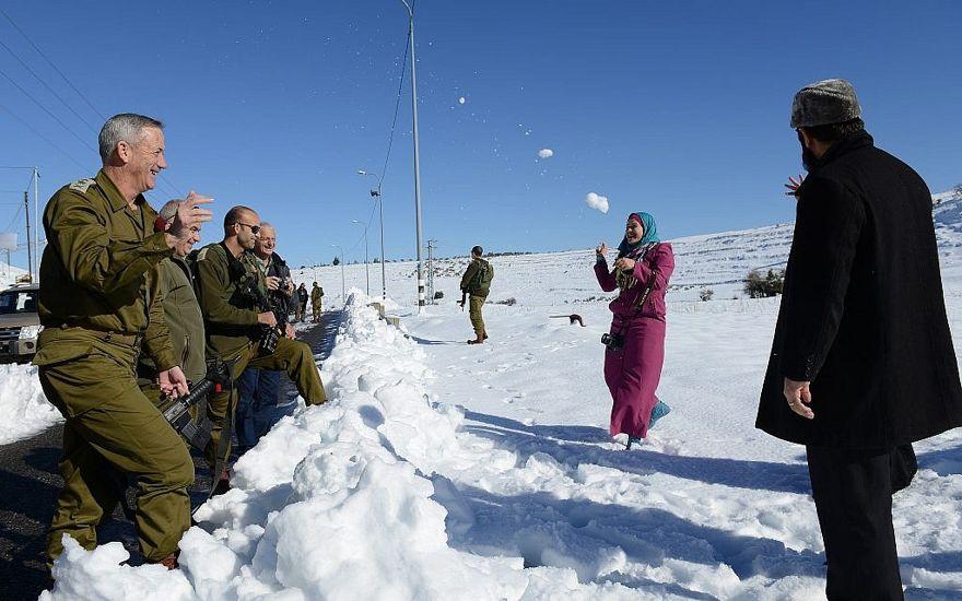 El entonces jefe de personal de las FDI Benny Gantz tiene una pelea de bolas de nieve con una familia de palestinos a lo largo de la ruta 60 de la Ribera Occidental, el 15 de diciembre de 2013. (Judah Ari Gross / Fuerzas de Defensa de Israel)