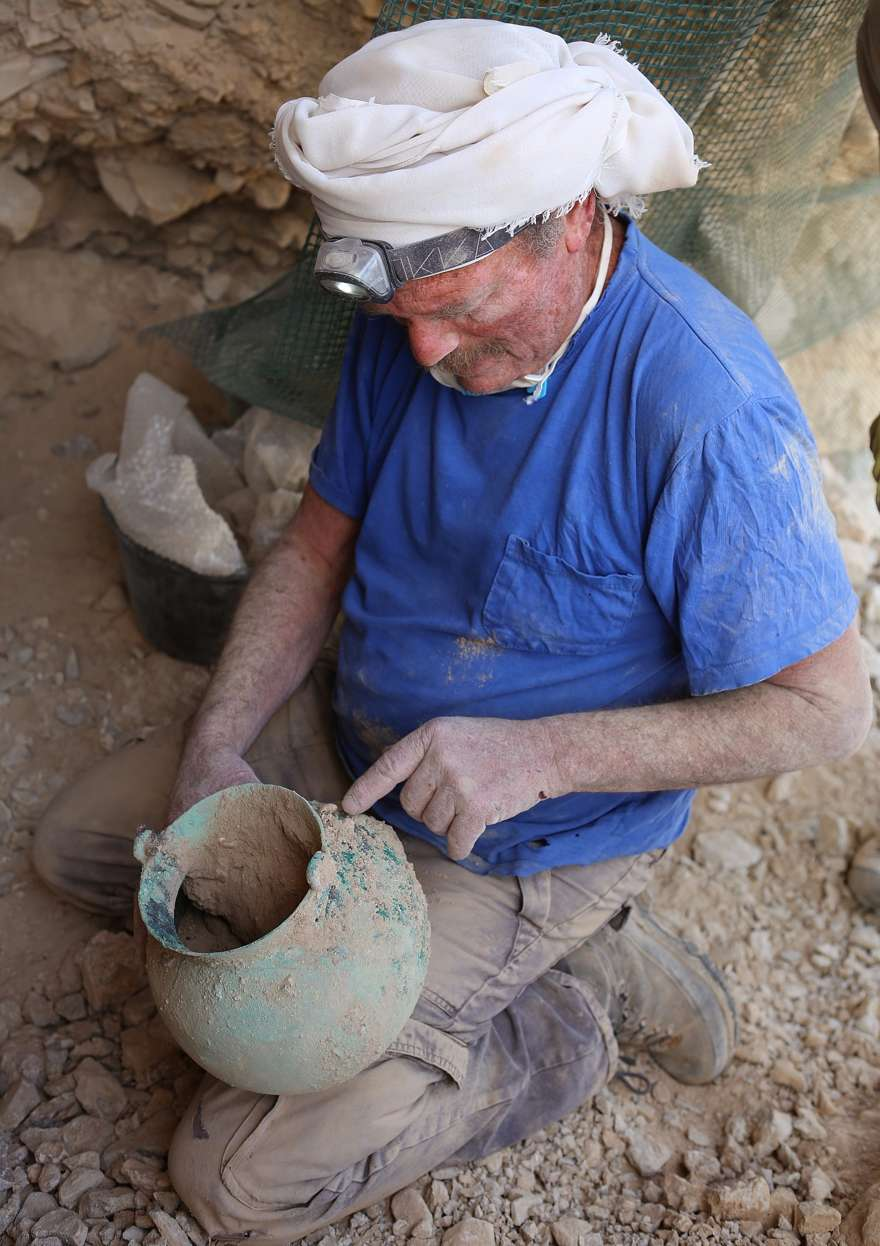 Yakov Kalman tiene la olla de bronce de 2.000 años de antigüedad descubierta en la Cueva 53B en Qumran, sobre el Mar Muerto. (Casey Olson)