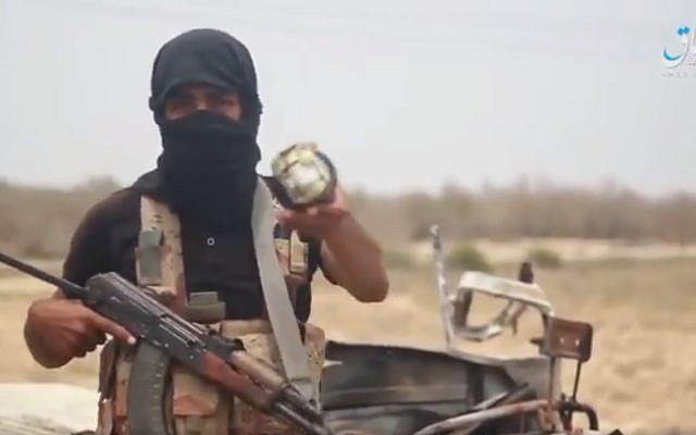 Un miembro del Sinaí afiliado al Estado Islámico que pretende mostrar municiones de fabricación israelí encontradas en los escombros de un ataque aéreo en un video publicado por la agencia de noticias Amaq el 23 de mayo de 2018. (captura de pantalla, Amaq)