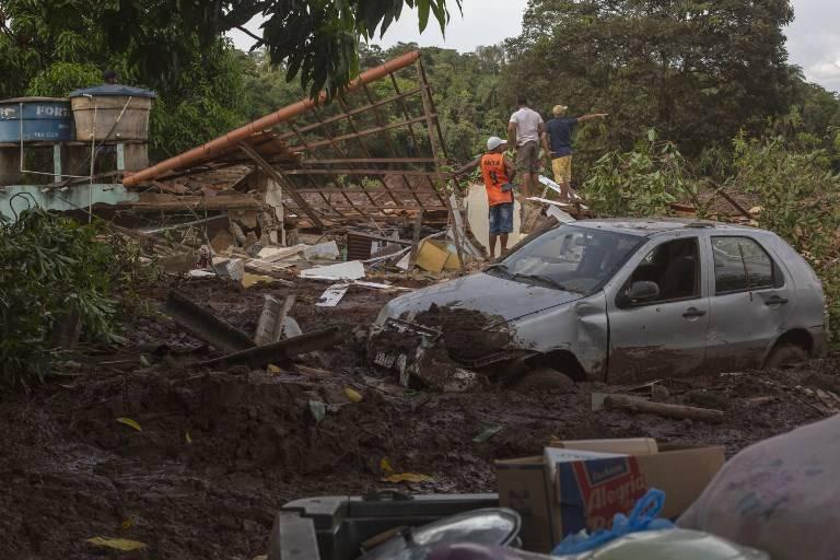 La gente de la comunidad del Parque da Cachoeira mira el área afectada por el lodo un día después del derrumbe de una represa en una mina de mineral de hierro perteneciente a la gigante minera brasileña Vale, cerca de la ciudad de Brumadinho en el estado de Minas Gerias, en el sureste de Brasil. , el 26 de enero de 2019. (Mauro Pimentel / AFP)