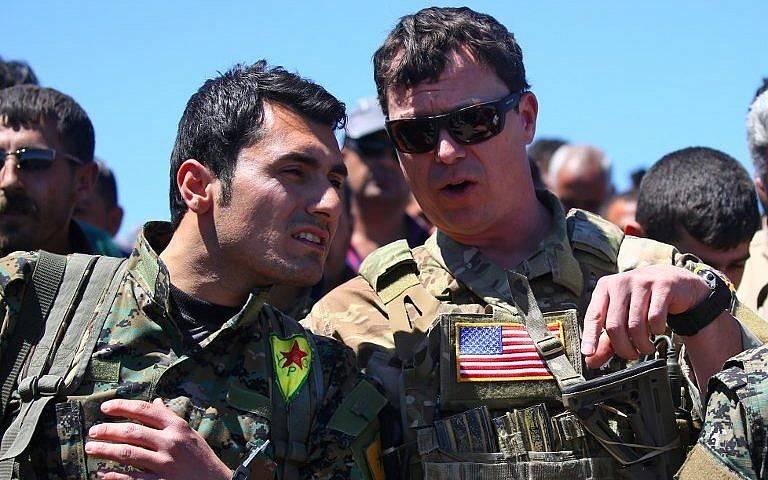 Una foto de archivo tomada el 25 de abril de 2017, muestra a un oficial militar de los EE. UU. (R) hablando con un combatiente de las Unidades de Protección del Pueblo Kurdo (YPG) en el sitio de ataques aéreos turcos cerca de la ciudad kurda de Derik, en el noreste de Siria, conocido como al- Malikiyah en árabe.(Delil Souleiman / AFP)