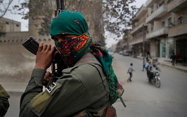 Un miembro de las fuerzas de seguridad internas kurdas sostiene su waepon durante una patrulla en Manbij, norte de Siria, 28 de marzo de 2018, (Foto AP / Hussein Malla)