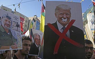En esta foto del 17 de julio de 2018, los manifestantes palestinos muestran retratos del fallecido líder palestino Yasser Arafat y del presidente de Estados Unidos Donald Trump durante un mitin en apoyo del partido Fatah en la ciudad de Nablus, en la Ribera Occidental. (Foto de AFP / Jaafar Ashtiyeh)