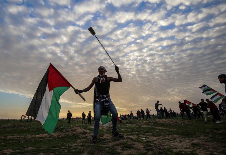 Un manifestante palestino porta una bandera nacional y una honda durante una manifestación cerca de la cerca a lo largo de la frontera con Israel, al este de la ciudad de Gaza, el 1 de febrero de 2019. (Dijo KHATIB / AFP)