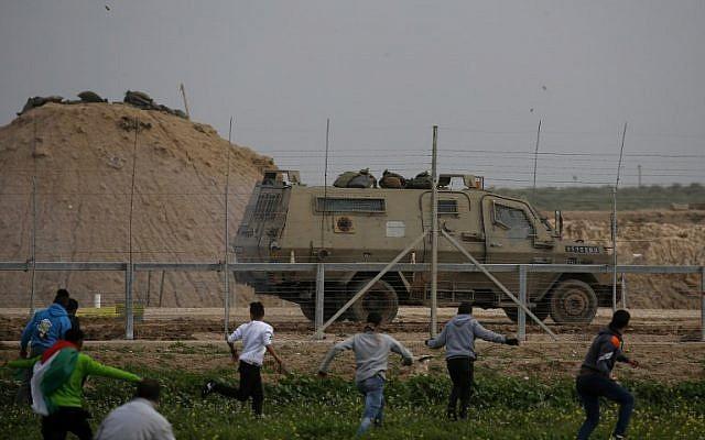 Los terroristas palestinos corren hacia la cerca a lo largo de la frontera con Israel, al este de la ciudad de Gaza, el 15 de febrero de 2019. Un vehículo militar israelí aparece en el otro lado de la cerca. (Dijo Khatib / AFP)