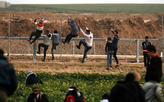 Los terroristas palestinos se suben a la valla de seguridad a lo largo de la frontera entre Israel y la Franja de Gaza, durante los ataques al este de la ciudad de Gaza, el 15 de febrero de 2019. (Said Khatib / AFP)