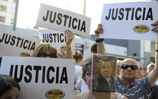 """La gente sostiene pancartas que decían """"Justicia"""" durante un mitin frente a la sede de la Asociación Mutual de Israelitas (AMIA) en Buenos Aires, el 21 de enero de 2015. (Crédito de la foto: Alejandro Pagni / AFP)."""