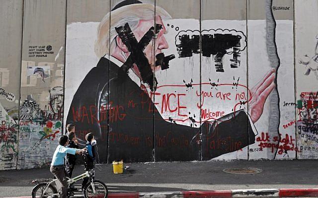 Los niños palestinos miran graffiti que representan al presidente de los EE. UU. Donald Trump y lemas contra el vicepresidente de los EE. UU., Mike Pence, pintados sobre la barrera de seguridad de Israel en la ciudad cisjordana de Belén durante enfrentamientos con manifestantes palestinos cerca de un punto de control israelí el 7 de diciembre de 2017. (AFP / Thomas Coex ) La Autoridad Palestina se ha negado a