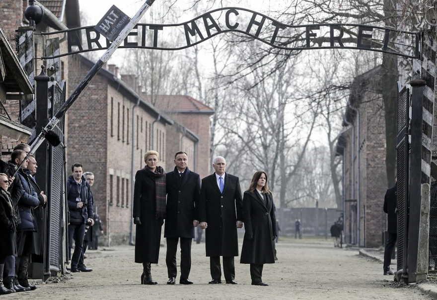 El vicepresidente de los EE. UU., Mike Pence, y su esposa Karen Pence, a la derecha, apoyan al presidente de Polonia, Andrzej Duda, y a su esposa, Agata Kornhauser-Duda, a la izquierda, bajo la puerta durante su visita al campo de concentración nazi Auschwitz-Birkenau en Oswiecim, Polonia, el viernes 15 de febrero de 2019. (Foto AP / Michael Sohn)
