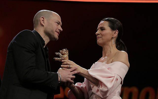 El director Nadav Lapid, a la izquierda, recibe el oso dorado a la mejor película para 'Sinónimos' de parte de la presidenta del jurado, Juliette Binoche, en la ceremonia de entrega de premios del Festival de Cine Berlinale 2019 en Berlín, Alemania, sábado 16 de febrero de 2019. (AP / Markus Schreiber)