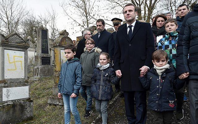 El presidente francés, Emmanuel Macron, toma a los niños de las manos mientras visita el cementerio judío destrozado en Quatzenheim, este de Francia, el martes 19 de febrero de 2019. (Frederick Florin, Pool vía AP)