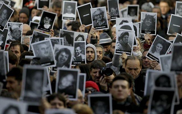 La gente muestra fotos de los que murieron en el atentado con bomba del centro judío de AMIA que mató a 85 personas cuando conmemoraban el 22 aniversario del ataque en Buenos Aires, Argentina, 18 de julio de 2016. (Foto AP / Natacha Pisarenko)