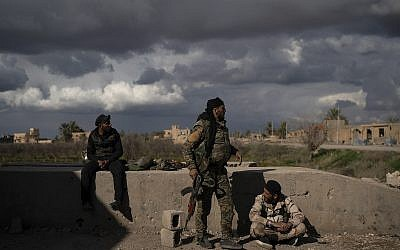 Los combatientes apoyados por las Fuerzas Democráticas Sirias (SDF) respaldados por los EE. UU se encuentran en un área recientemente tomada por SDF de los militantes del Estado Islámico como continuación en la aldea de Baghouz, Siria, el 17 de febrero de 2019. (Foto AP / Felipe Dana)