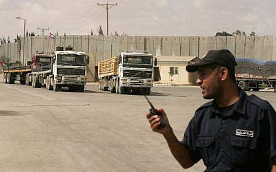 Un policía palestino leal a Hamás monta guardia cuando los camiones que transportan materiales de construcción ingresan a la Franja de Gaza a través del cruce de Kerem Shalom el 22 de septiembre de 2013. (Abed Rahim Khatib / Flash90 / File)