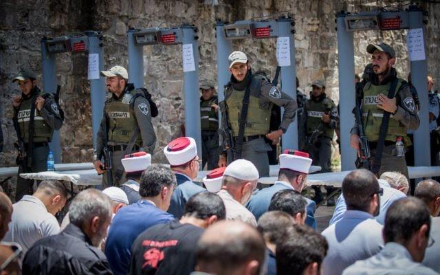 Los funcionarios de Waqf dirigen las oraciones musulmanas fuera del Monte del Templo en la Ciudad Vieja de Jerusalem el 16 de julio de 2017 después de negarse a pasar por las puertas de detectores de metales instaladas por la policía israelí. (Yonatan Sindel / Flash90)