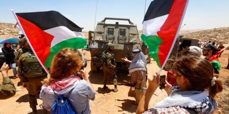 """FOTO: """"Turistas"""" protestan contra Israel cerca de Hebrón el 7 de julio de 2018. (Wisam Hashlamoun / Flash90)"""