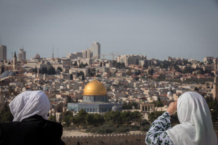 Los turistas miran una vista de la Cúpula de la Roca y el Monte del Templo desde el mirador del Monte de los Olivos que domina la ciudad vieja de Jerusalén, el 28 de noviembre de 2018. (Yonatan Sindel / Flash90)
