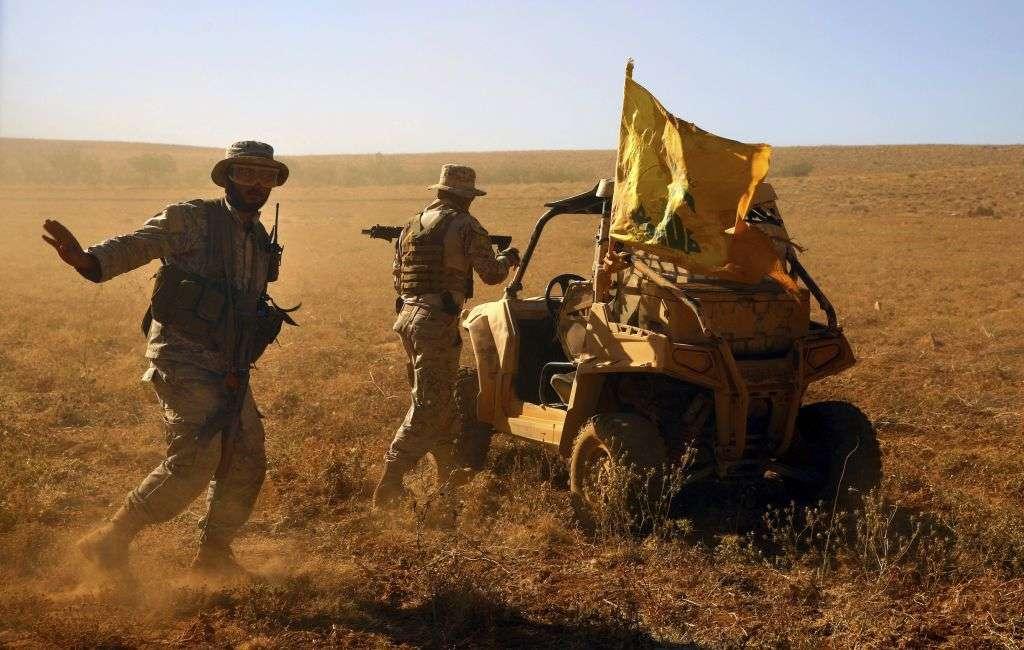 Combatientes de Hezbolá están parados junto a su vehículo militar en el valle de Al-Kheil en la frontera entre el Líbano y Siria, el 29 de julio de 2017. (Foto AP / Bilal Hussein)