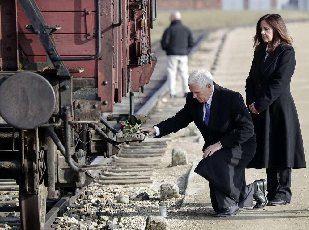 El vicepresidente de los EE. UU., Mike Pence, se arrodilla junto a su esposa Karen, a la derecha, en un vagón de carga que solía transportar judíos; durante su visita al antiguo campo de exterminio nazi de Auschwitz-Birkenau en Oswiecim, Polonia, el viernes 15 de febrero de 2019. (Foto AP) / Michael Sohn)