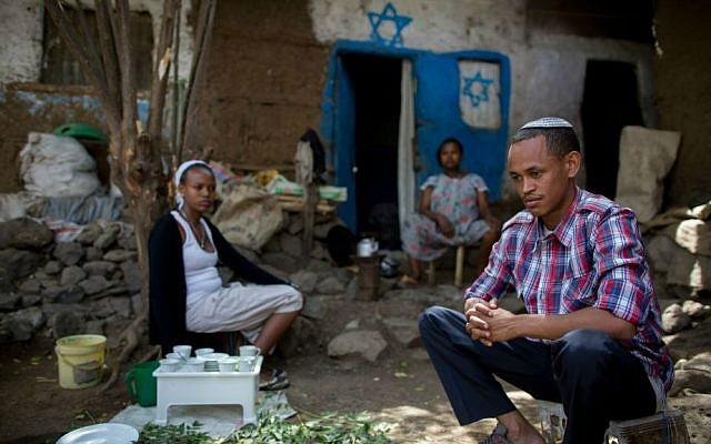 Atenkut Setataw (derecha), con su esposa Alesa Netere (izquierda) y un vecino fuera de su casa en Gondar el 24 de abril de 2016. Setataw pintó la casa. (Miriam Alster / Flash90)
