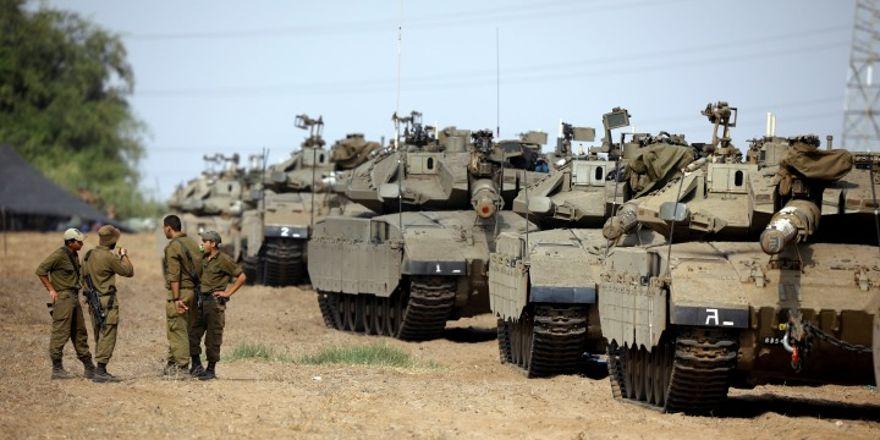 Los soldados de las FDI hablan junto a una línea de tanques en un área abierta cerca de la frontera de Israel con la Franja de Gaza, el 18 de octubre de 2018. Foto: Reuters / Amir Cohen.