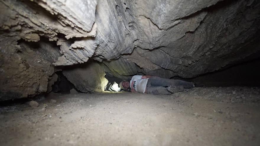 Un investigador pasa por una estrecha abertura en la cueva de Malcham el 22 de marzo de 2019, cerca del Mar Muerto. (Cortesía Anton Chikishev / Universidad Hebrea)