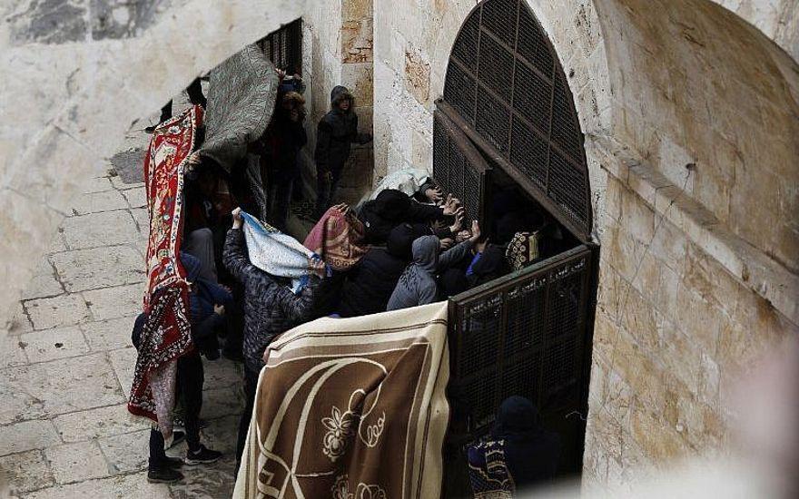 Los palestinos rompen una puerta de la Puerta de la Misericordia en el Monte del Templo en la Ciudad Vieja de Jerusalem el 15 de marzo de 2019. (Ahmad Gharabli / AFP)