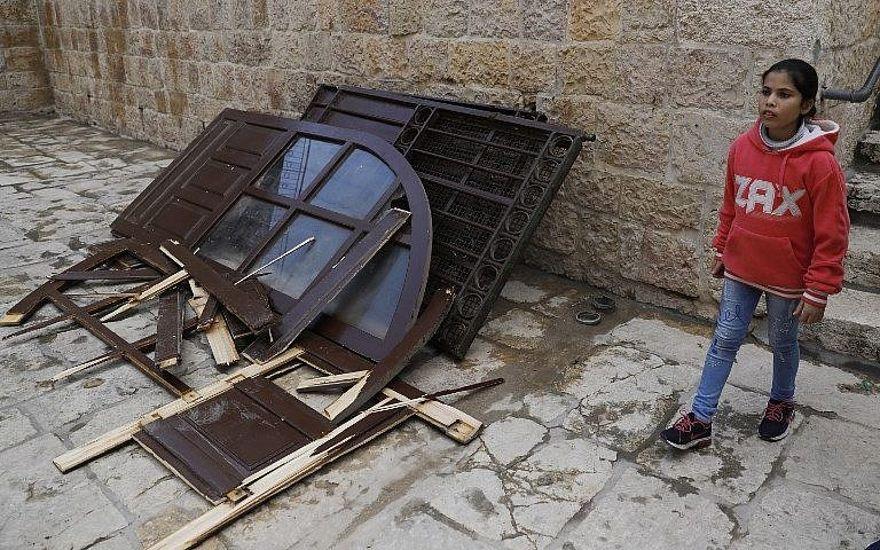 Una niña pasa junto a una puerta que los palestinos musulmanes rompieron en la Puerta de la Misericordia en el Monte del Templo en la Ciudad Vieja de Jerusalem el 15 de marzo de 2019. (Ahmad Gharabli / AFP)