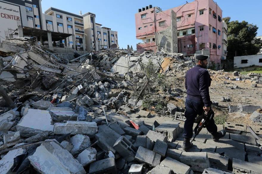 Una fotografía tomada el 26 de marzo de 2019, muestra a un policía de Hamas haciendo guardia junto a los escombros de un edificio en la ciudad de Gaza que fue atacado la noche anterior por un ataque aéreo israelí. (Mahmud Hams / AFP)