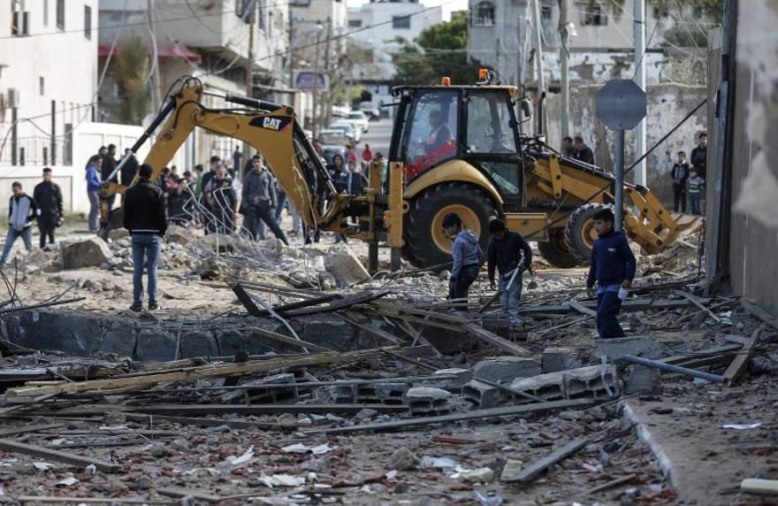 Una fotografía tomada el 26 de marzo de 2019 muestra a una excavadora limpiando escombros junto a la oficina destruida del líder de Hamas, Ismail Haniyeh, en la ciudad de Gaza, que fue atacada la noche anterior por un ataque aéreo israelí. (Mahmud Hams / AFP)