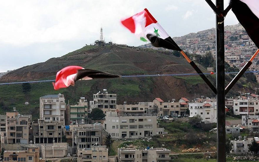 Las banderas sirias vuelan en la ciudad siria de Ain al-Tineh frente a Majdal Shams en los Altos del Golán israelíes el 26 de marzo de 2019. (Louai Beshara / AFP)