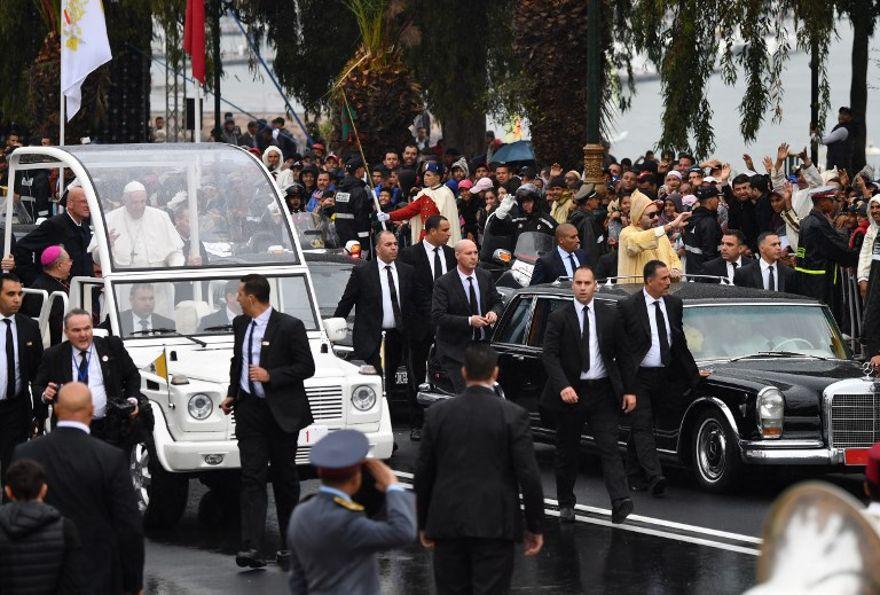 El rey Mohammed VI (R) saluda a la multitud desde su automóvil cuando llega con el Papa Francisco (L) en su papa móvil en la Plaza de Touran Hassan, a la llegada del pontífice al país norteafricano el 30 de marzo de 2019. (Alberto Pizzoli / AFP )