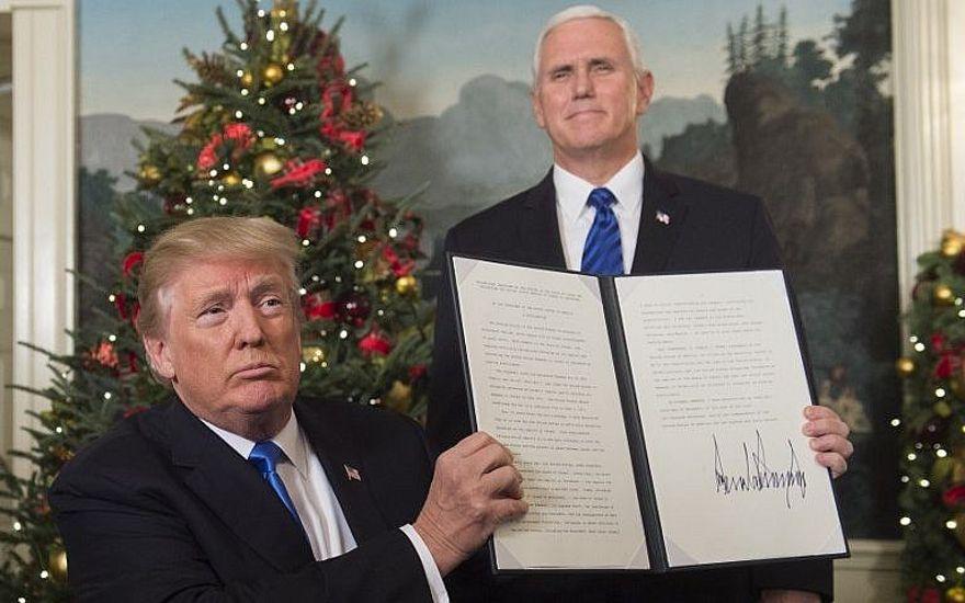 El presidente de los Estados Unidos, Donald Trump, sostiene un memorando firmado que reconoce a Jerusalem como la capital de Israel, mientras el vicepresidente de los Estados Unidos observa, en la Casa Blanca, el 6 de diciembre de 2017. (AFP Photo / Saul Loeb)
